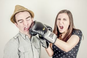 Photo of a woman jokingly punching a man in the face with boxing gloves on.