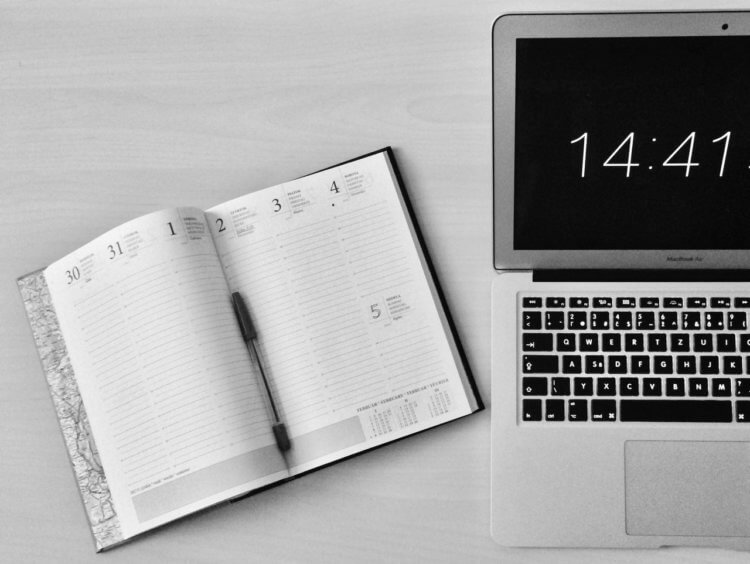 A laptop displaying the time and a planner journal lays next to it