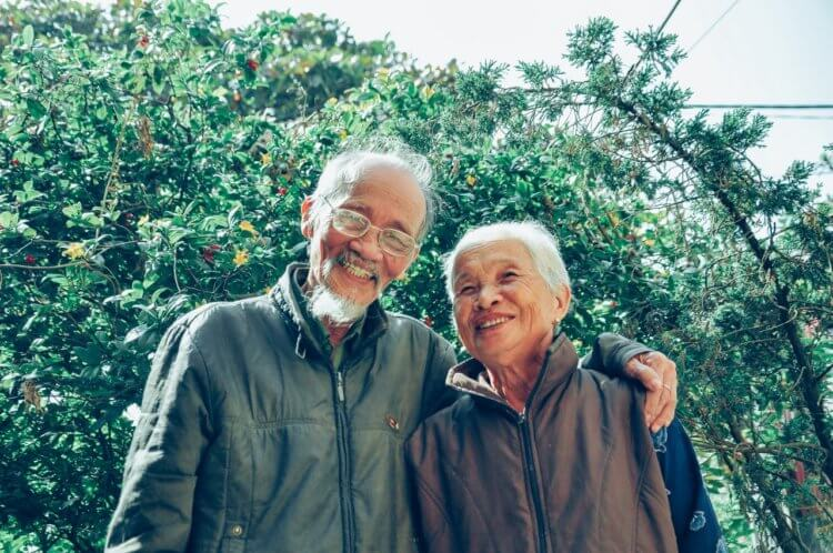 elderly couple in front of trees