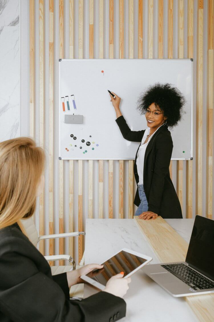 woman leading a team meeting in front of a white board